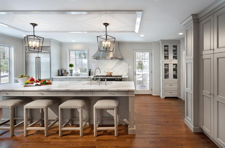 Long Gray Kitchen Island with Gray Upholstered Backless Stools .