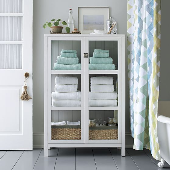 Clean-lined classic cabinet frames books, linens, cookware and .