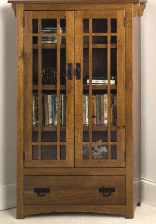 Mission Bookcase with drawer and wood framed glass doors .