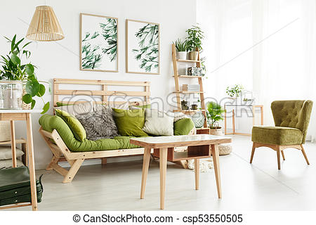 Natural living room with plants. Wooden table near green armchair .
