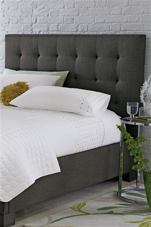 charcoal grey, upholstered headboard with white linens | Gray .