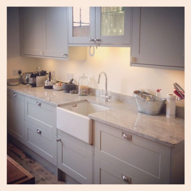 Painted light grey wood kitchen with marble worktops and wood .