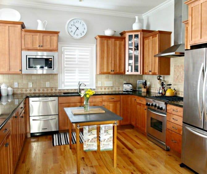 Kitchen with Wood Cabinets, Wood Floor, Dark Countertop and Beige .