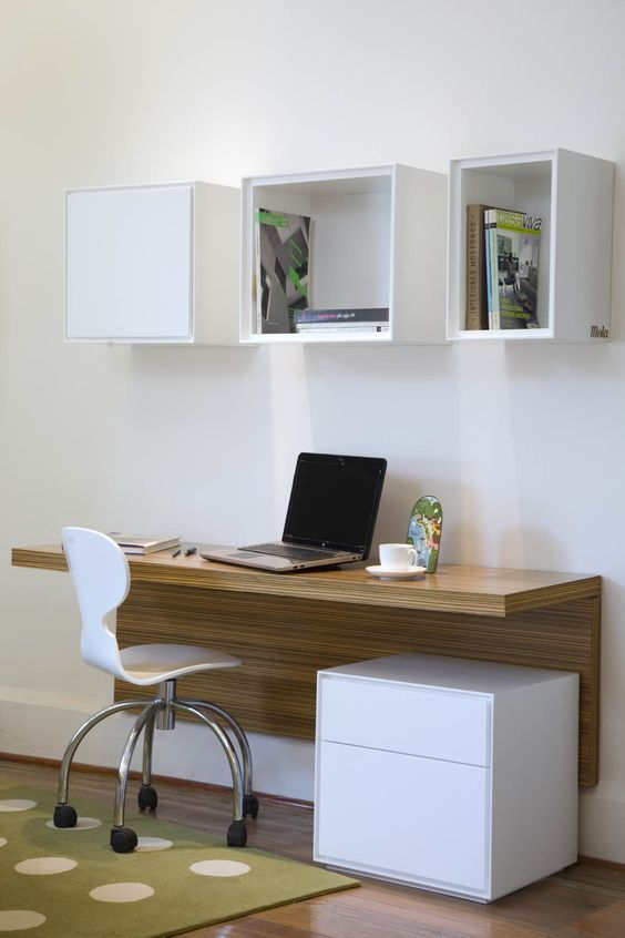 modern study space with a wall mounted desk and open box shelves .