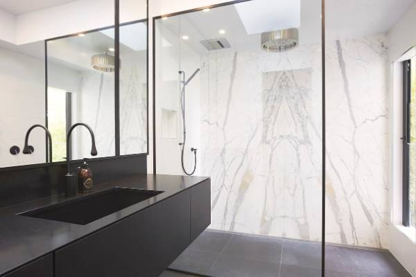 Black and white bathroom comes with black taps, shower and toilet .