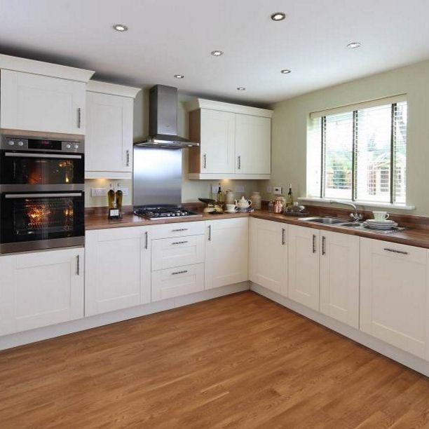 Wooden surface, cream cupboards, wooden floor and sage walls .