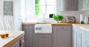 Country kitchen with grey painted cabinetry and wooden worktops .