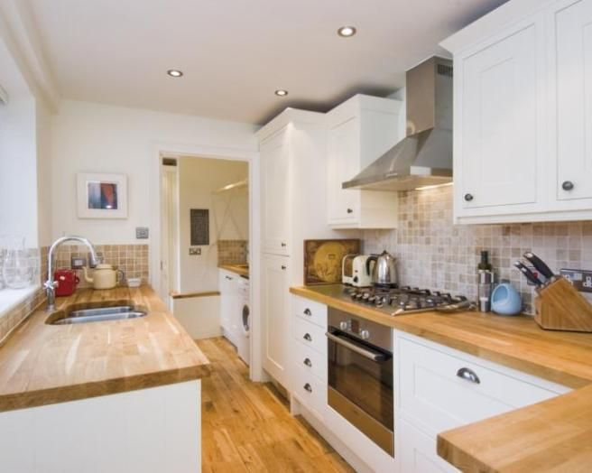 white kitchen, oak worktop and floor and beige wall tiles. very .