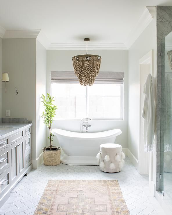 Gorgeous white and gray bathroom is illuminated by a brown beaded .