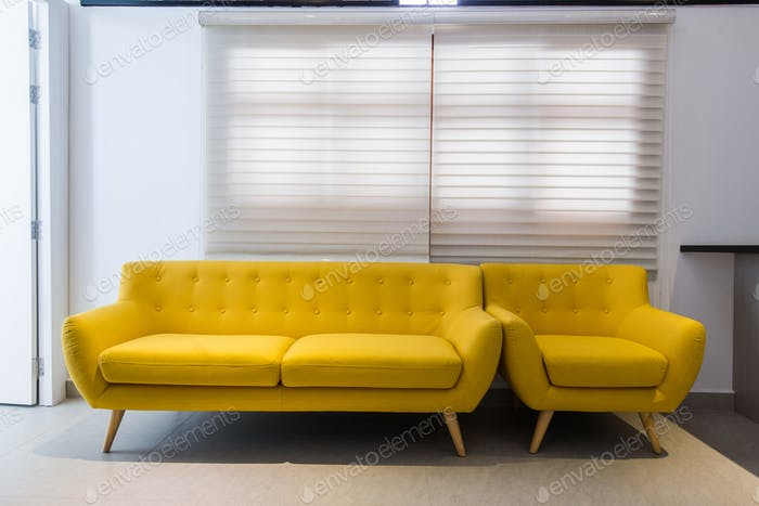 Modern yellow sofa and chair in room interior at home or hotel photo .